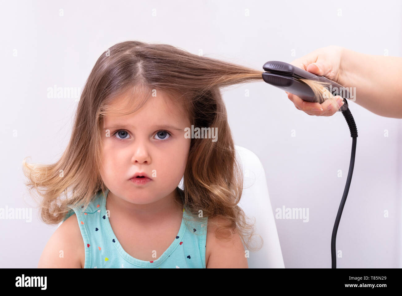 Mother Straightening Hair With Straightener To Her Daughter - Stock Image