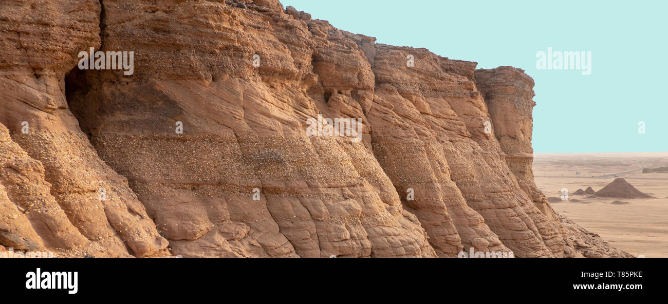 Exploration in a sandstone rock with a slope layer and intermediate banks of conglomerate, deposited close to the coast, with pyramids in the backgrou - Stock Image