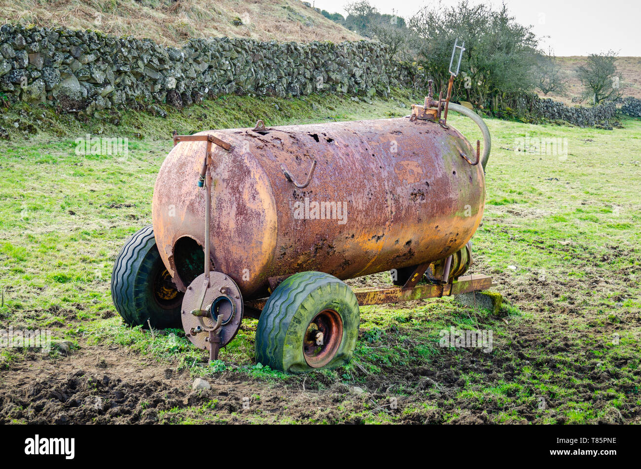 A rusty, corroded slurry tanker with punctured tyres sits abandoned in a muddy field in the Irish countryside. - Stock Image