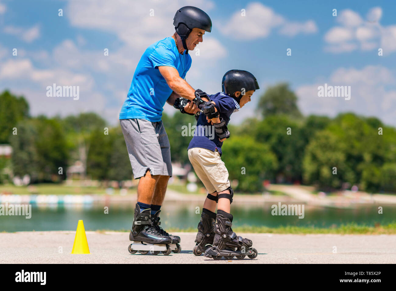 Grandfather teaching grandson to roller skate Stock Photo