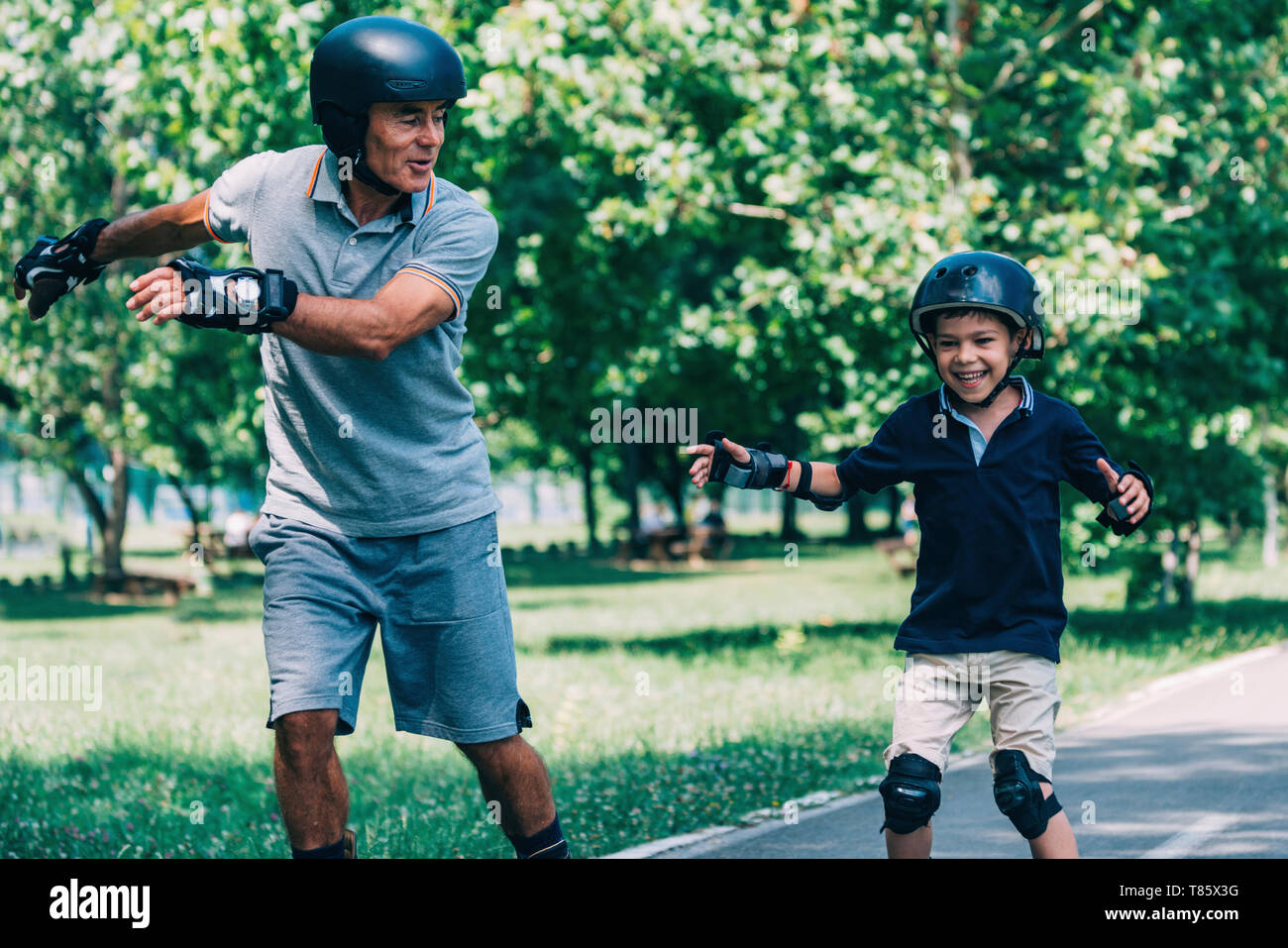 Grandfather and grandson roller skating Stock Photo