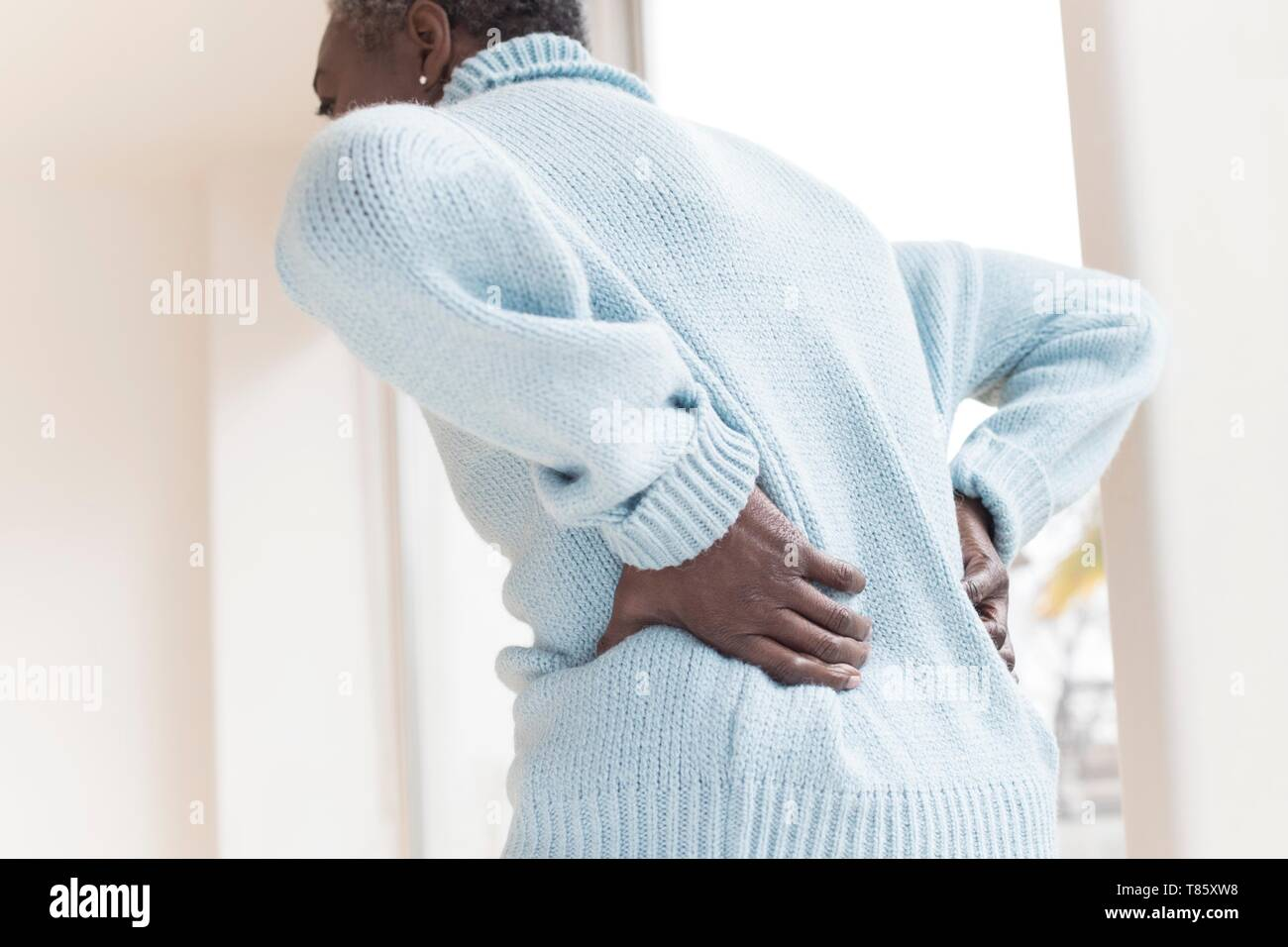 Woman with back pain - Stock Image