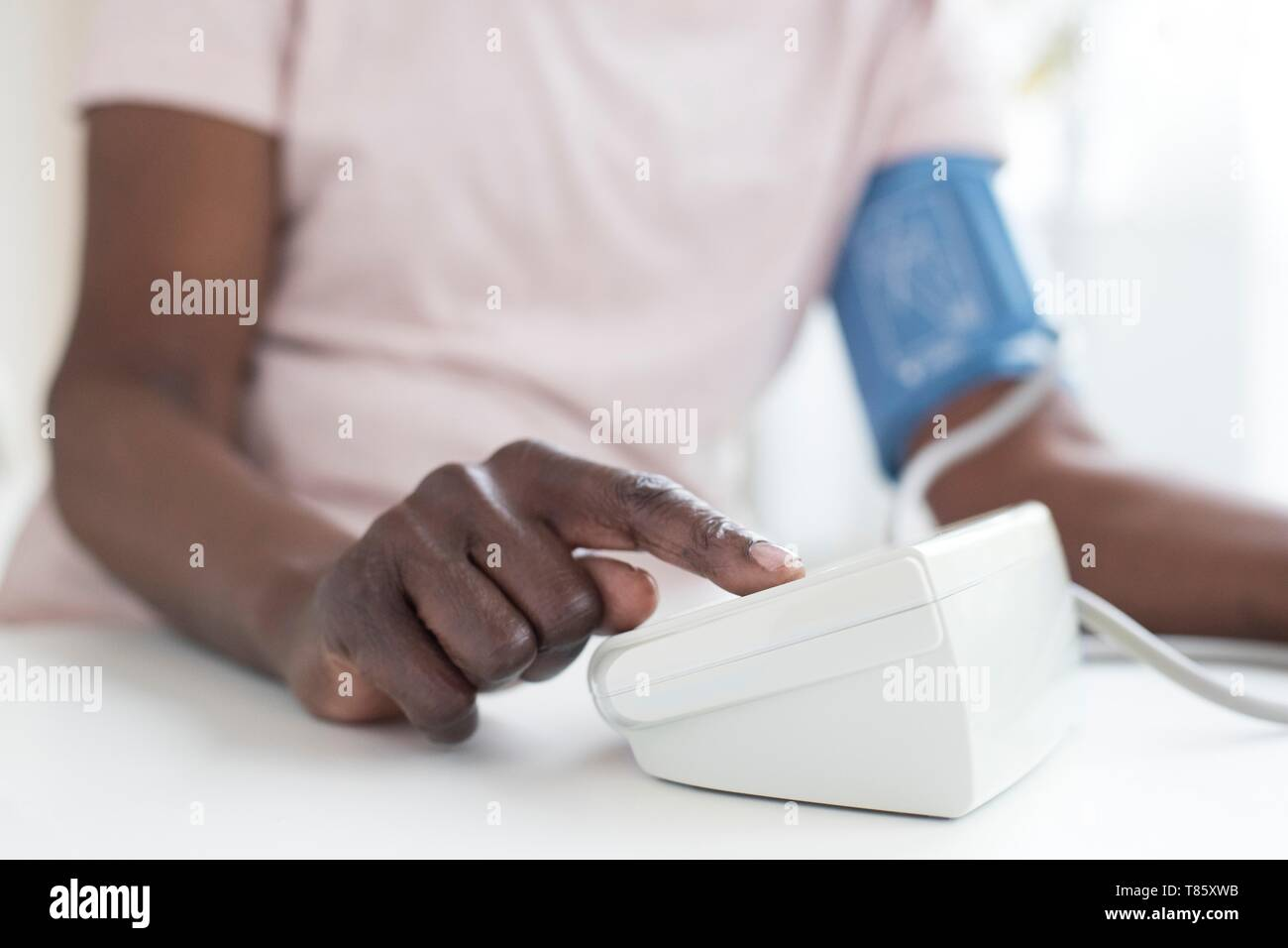 Woman testing blood pressure - Stock Image