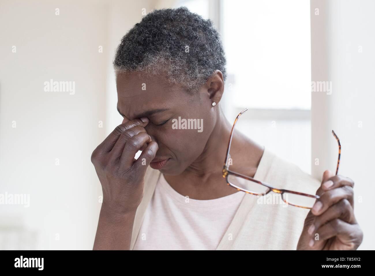 Woman touching bridge of nose - Stock Image