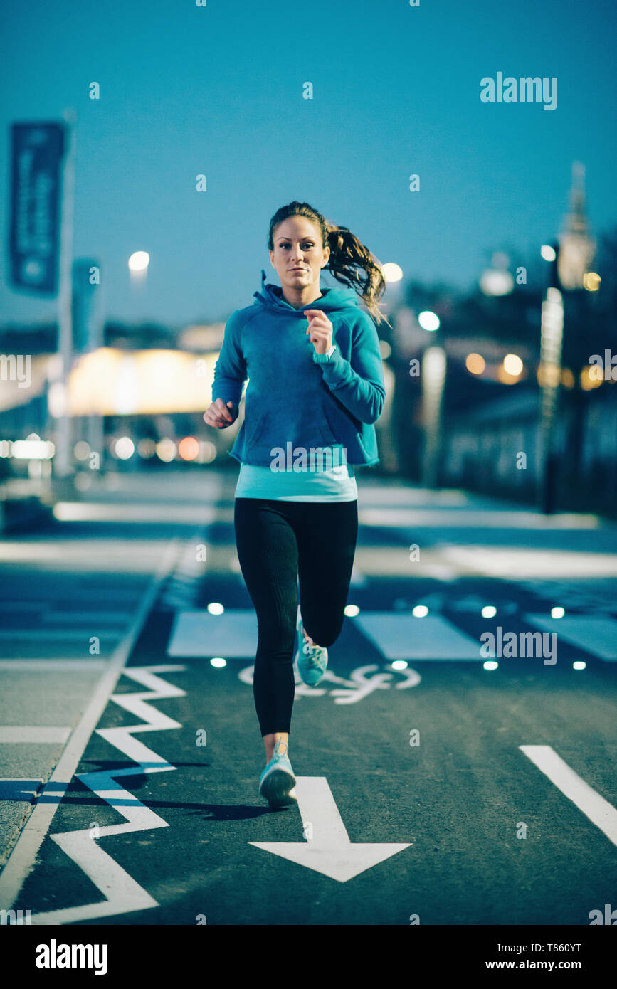 Woman jogging in city at night Stock Photo