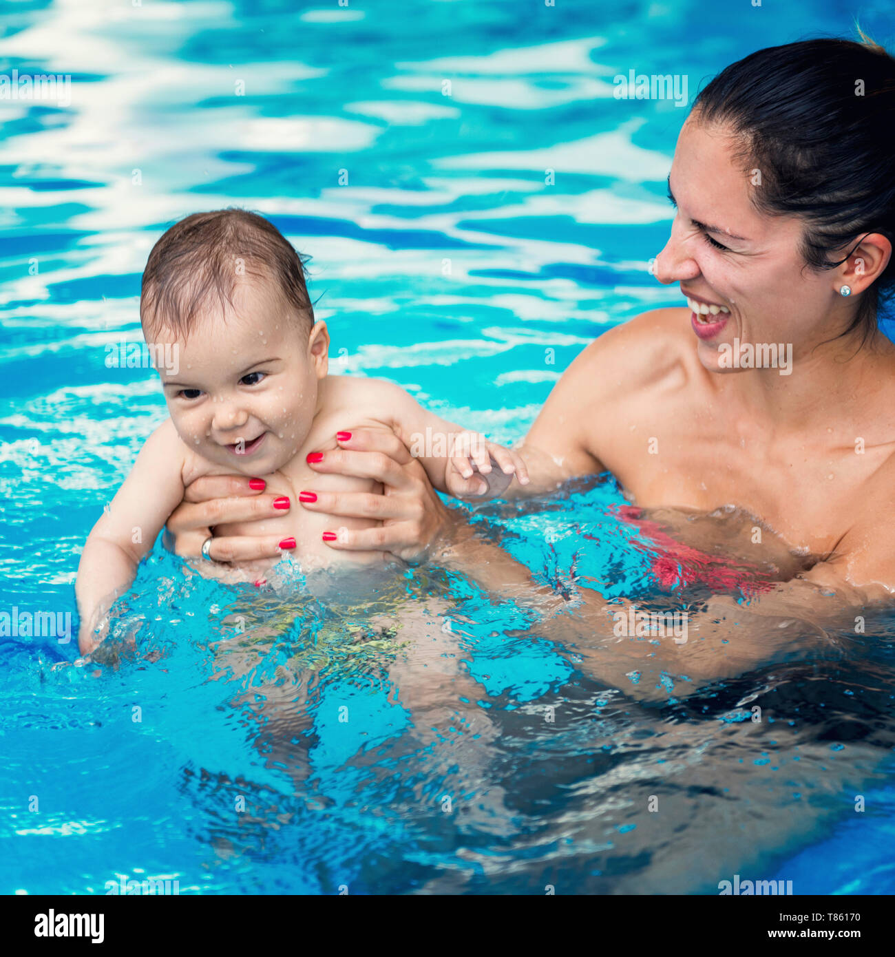 Baby boy and mother in swimming pool - Stock Image