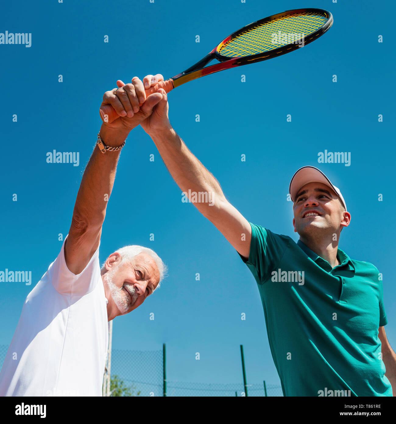 Senior man with tennis instructor - Stock Image