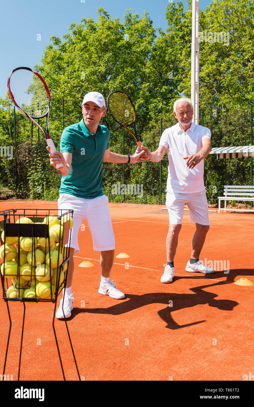 Senior man with tennis instructor - Stock Image