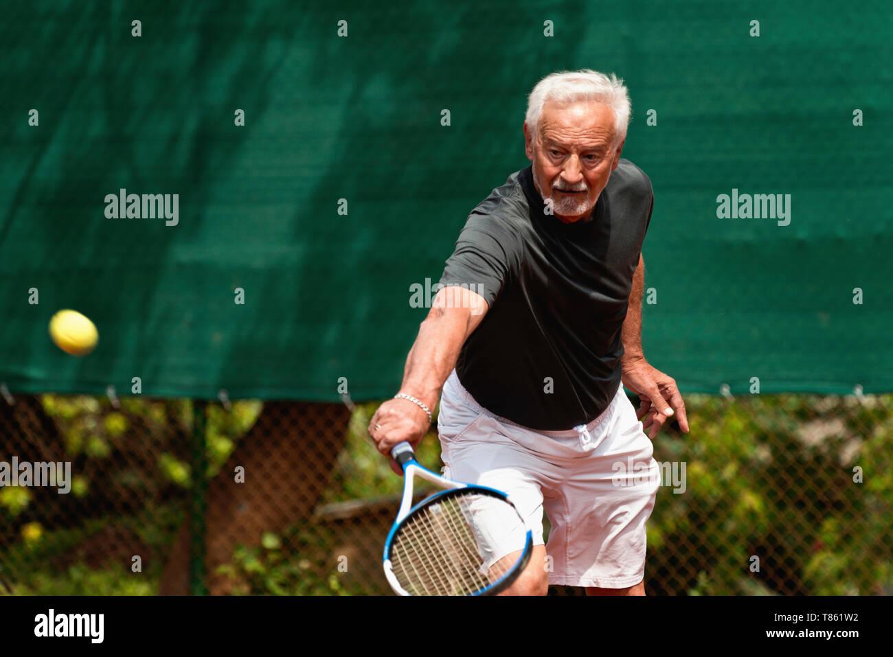 Active senior man playing tennis - Stock Image