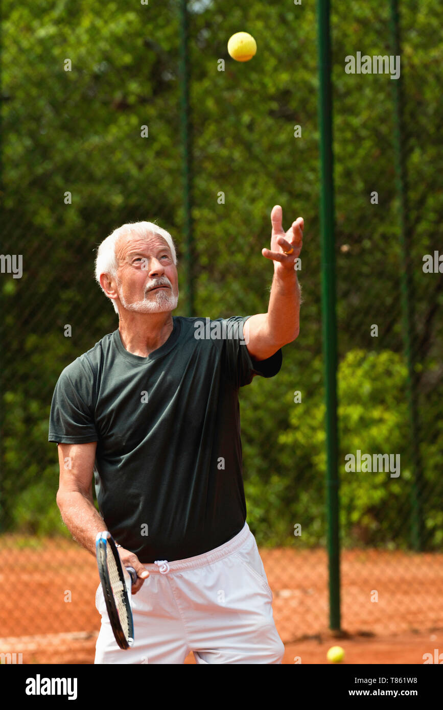 Active senior man playing tennis Stock Photo