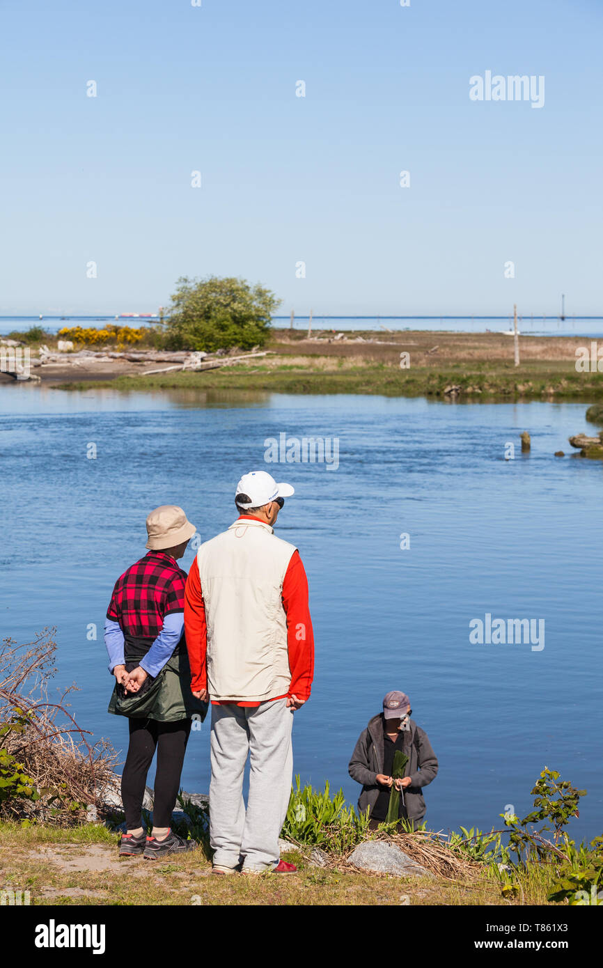 Older couple talking with a young fisherman in a tidal inlet at Steveston British Columbia Stock Photo