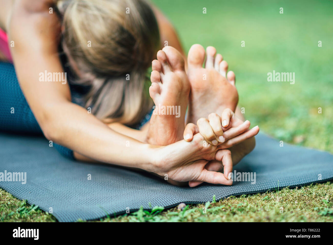 Yoga seated forward bend - Stock Image