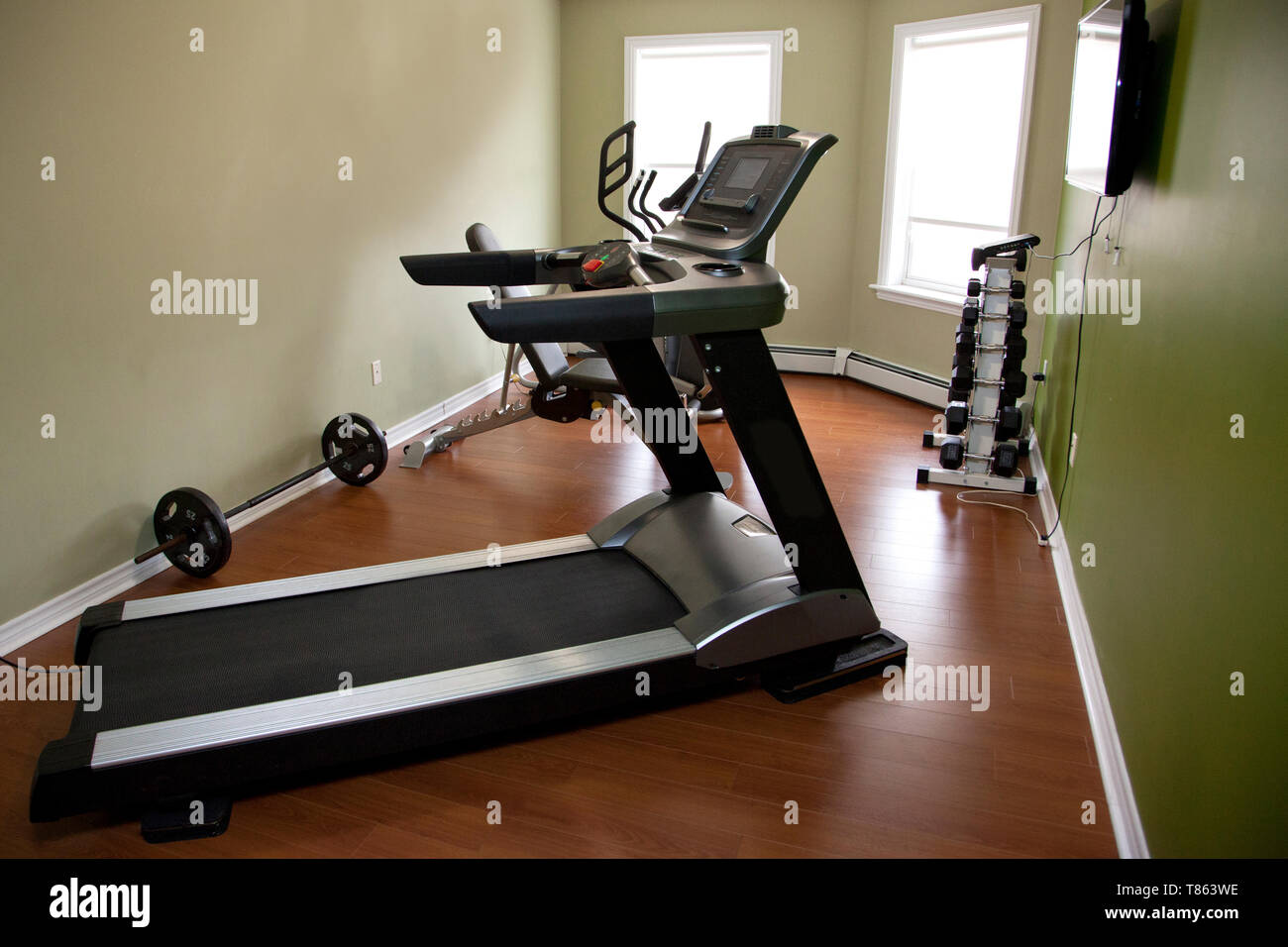 A treadmill in a home gym with other equipment inside an apartment