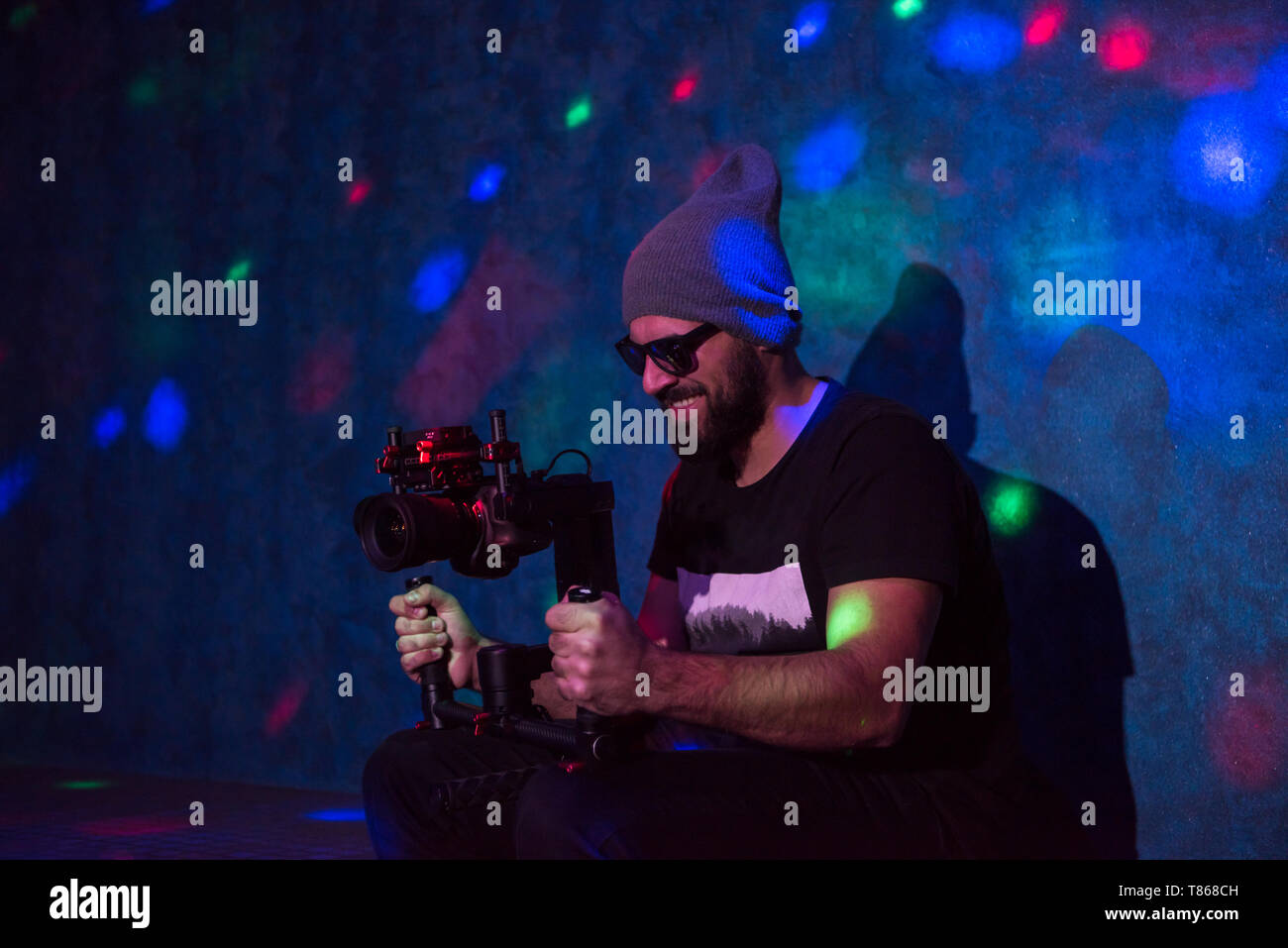 young videographer with gimball video slr working in kids neon disco party - Stock Image