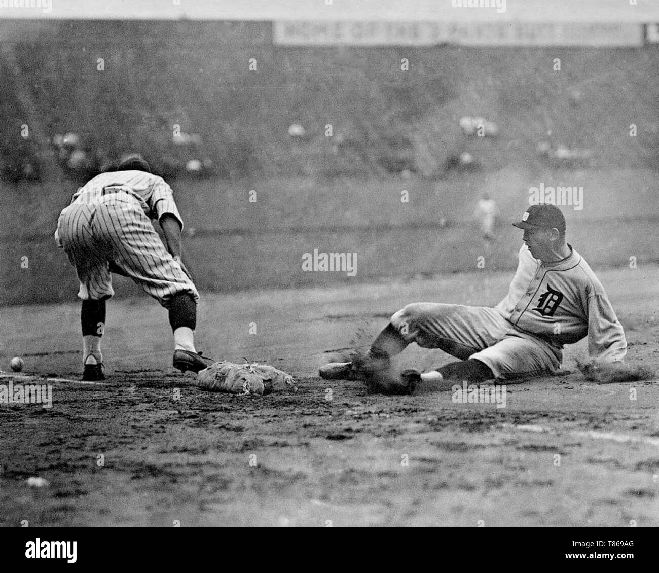 Detroit Tigers player slides safely into third base as a Washington Senators fielder reaches to the left for the ball during a baseball game 1910. Stock Photo