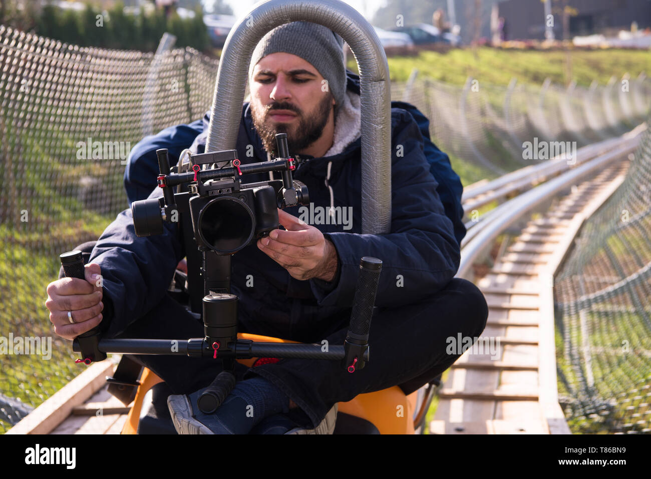 young videographer with gimball video slr at work on alpine coaster - Stock Image