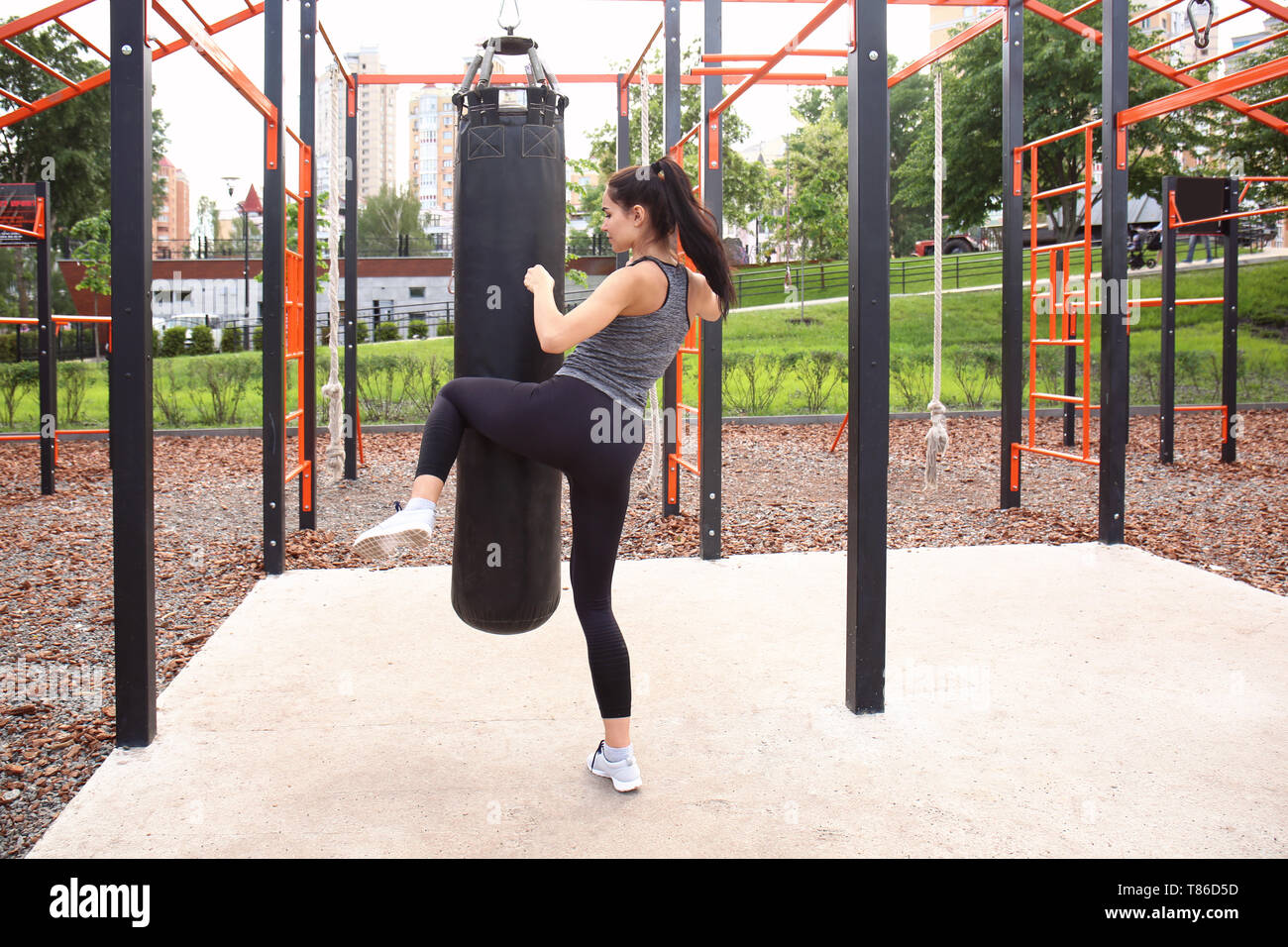 Sporty young woman training with punching bag on athletic field - Stock Image