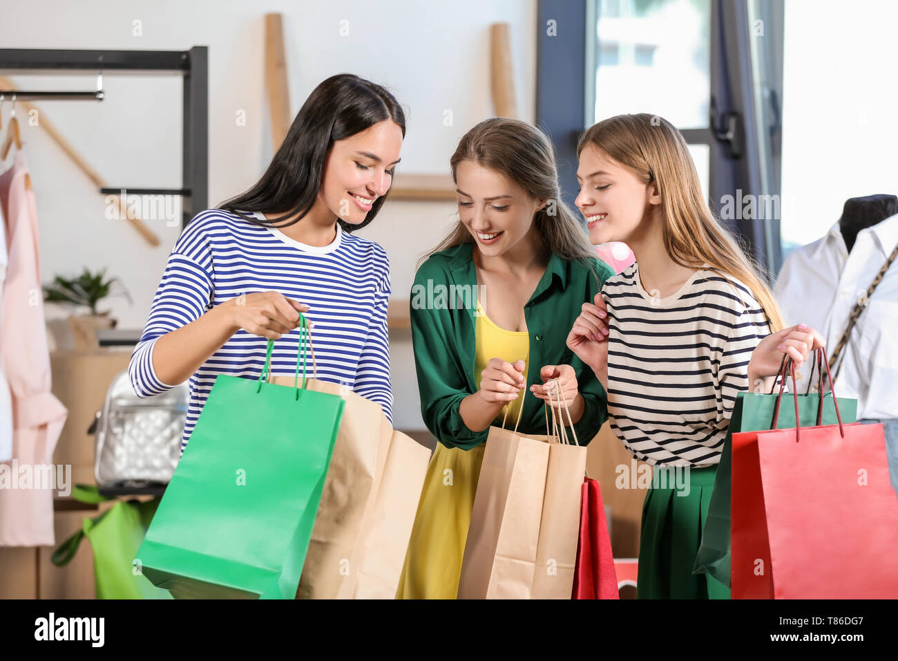 f3a7f7a712 Beautiful young women with shopping bags in clothing shop Stock ...