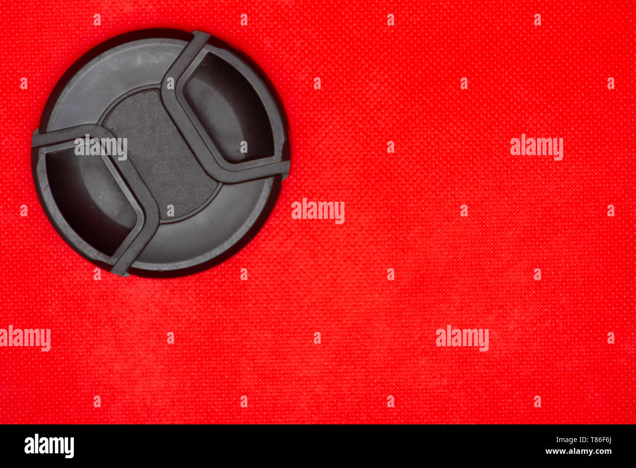 Close up of a black circle lens cap top left corner for DSLR camera lens on a rich red background. - Stock Image