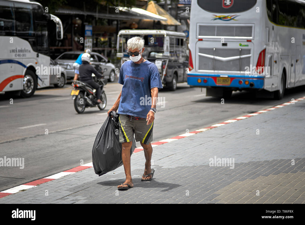 Man wearing a pollution facemask amongst traffic fumes Thailand Southeast Asia - Stock Image
