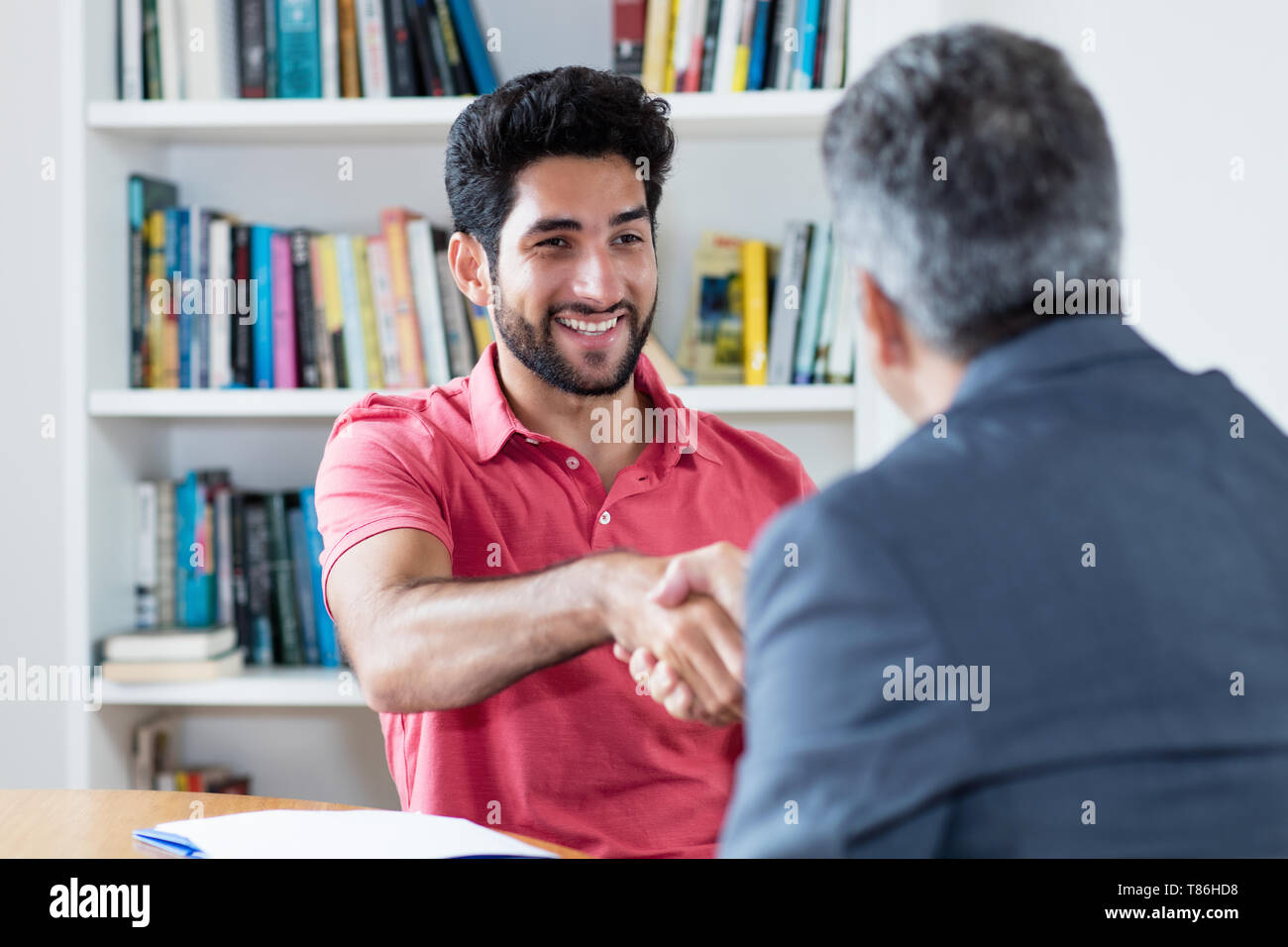 Handshake of latin american male apprentice after job interview with businessman at office - Stock Image