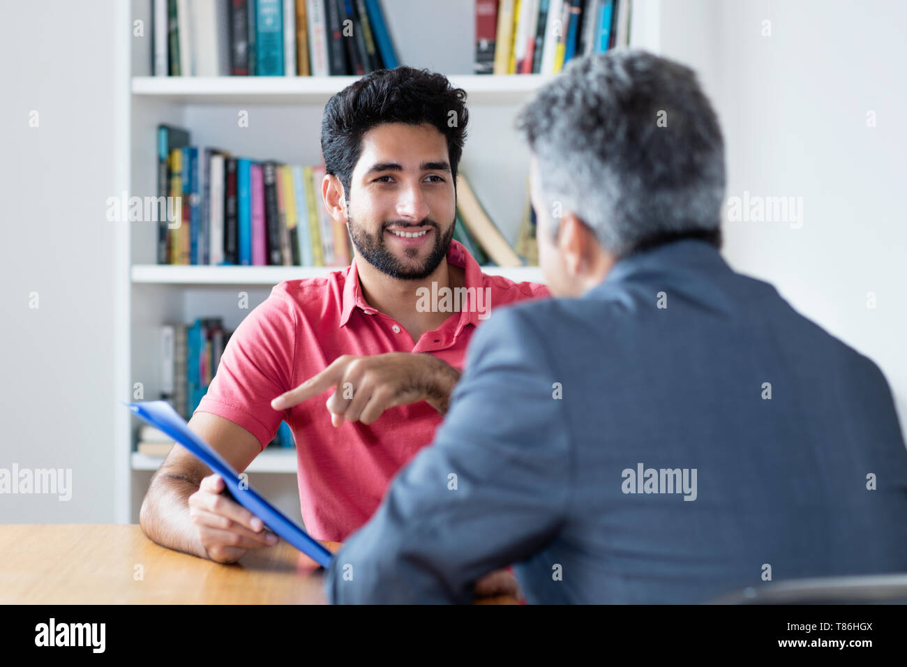 Job interview of latin american male apprentice with businessman at office - Stock Image