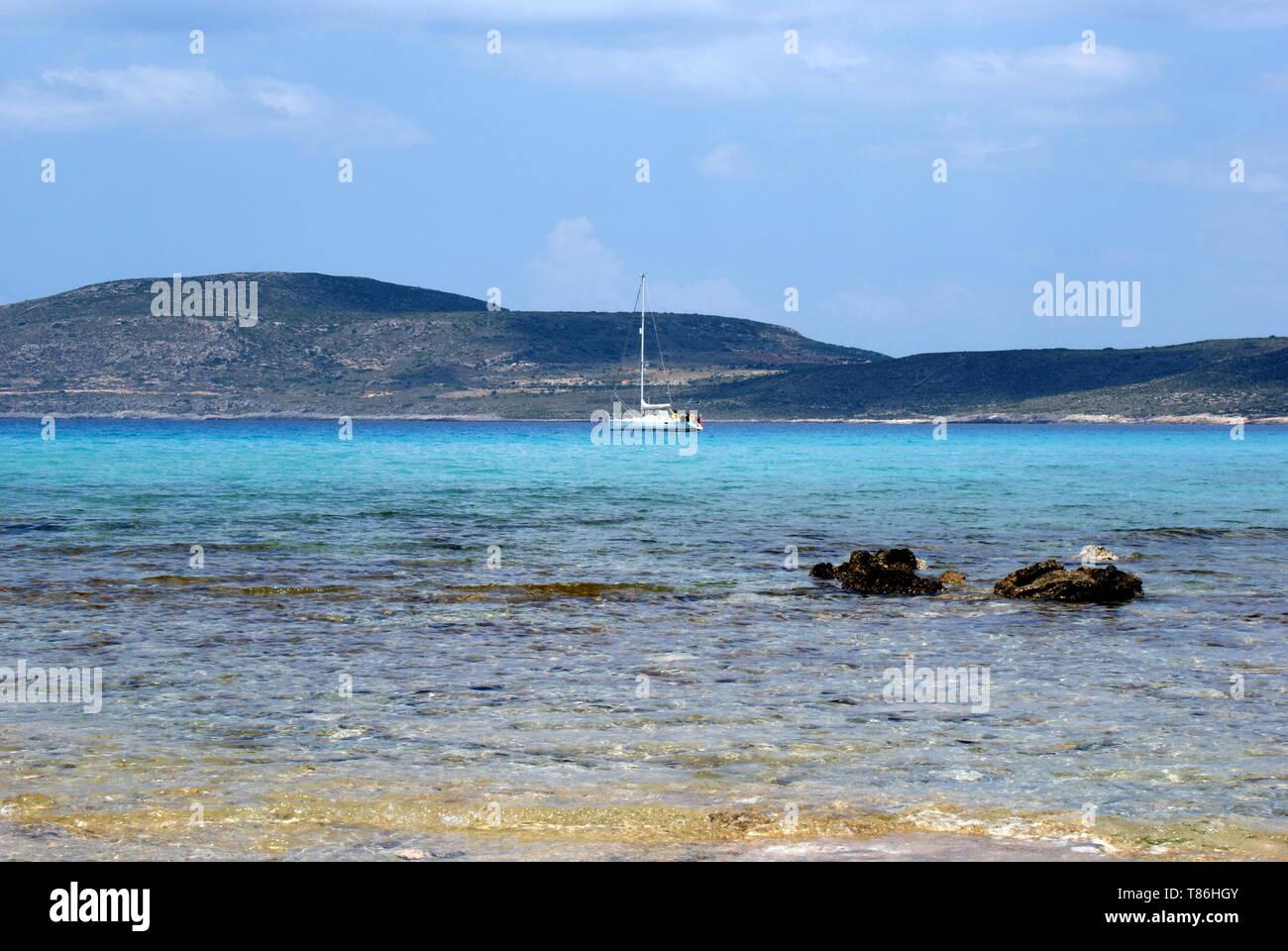 A sailing yacht anchored off Simos beach, Elafonisos island,    Laconia, Peloponnese, Greece - Stock Image