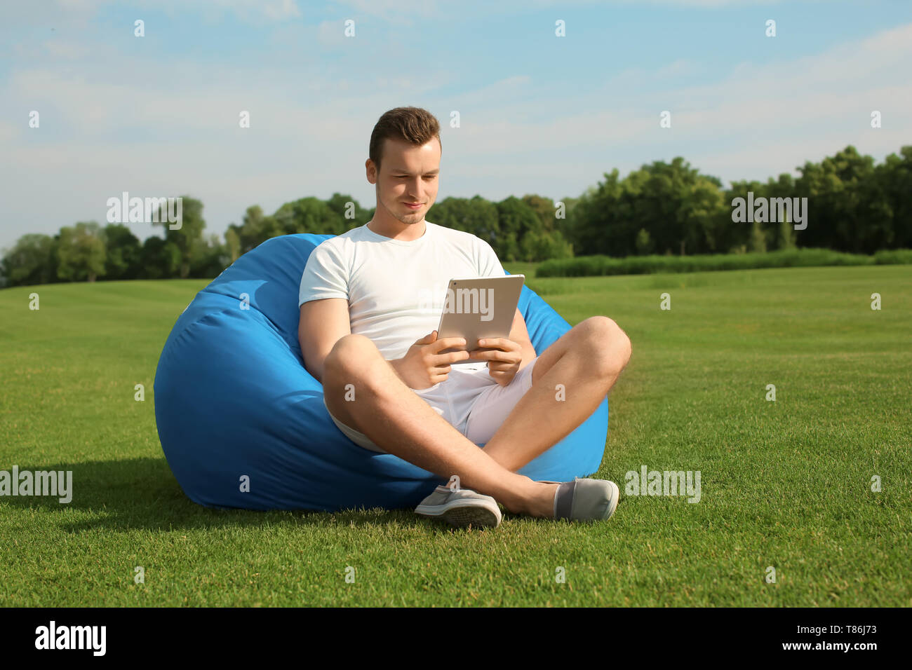 Young man with tablet PC resting on bean bag chair outdoors - Stock Image