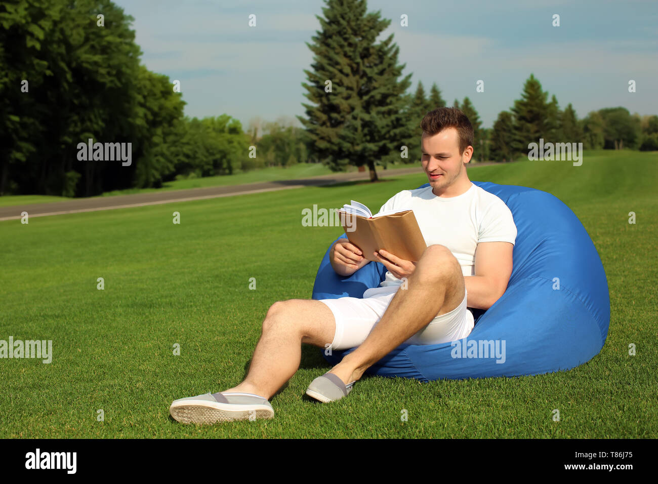 Young man reading book while sitting on bean bag chair outdoors - Stock Image
