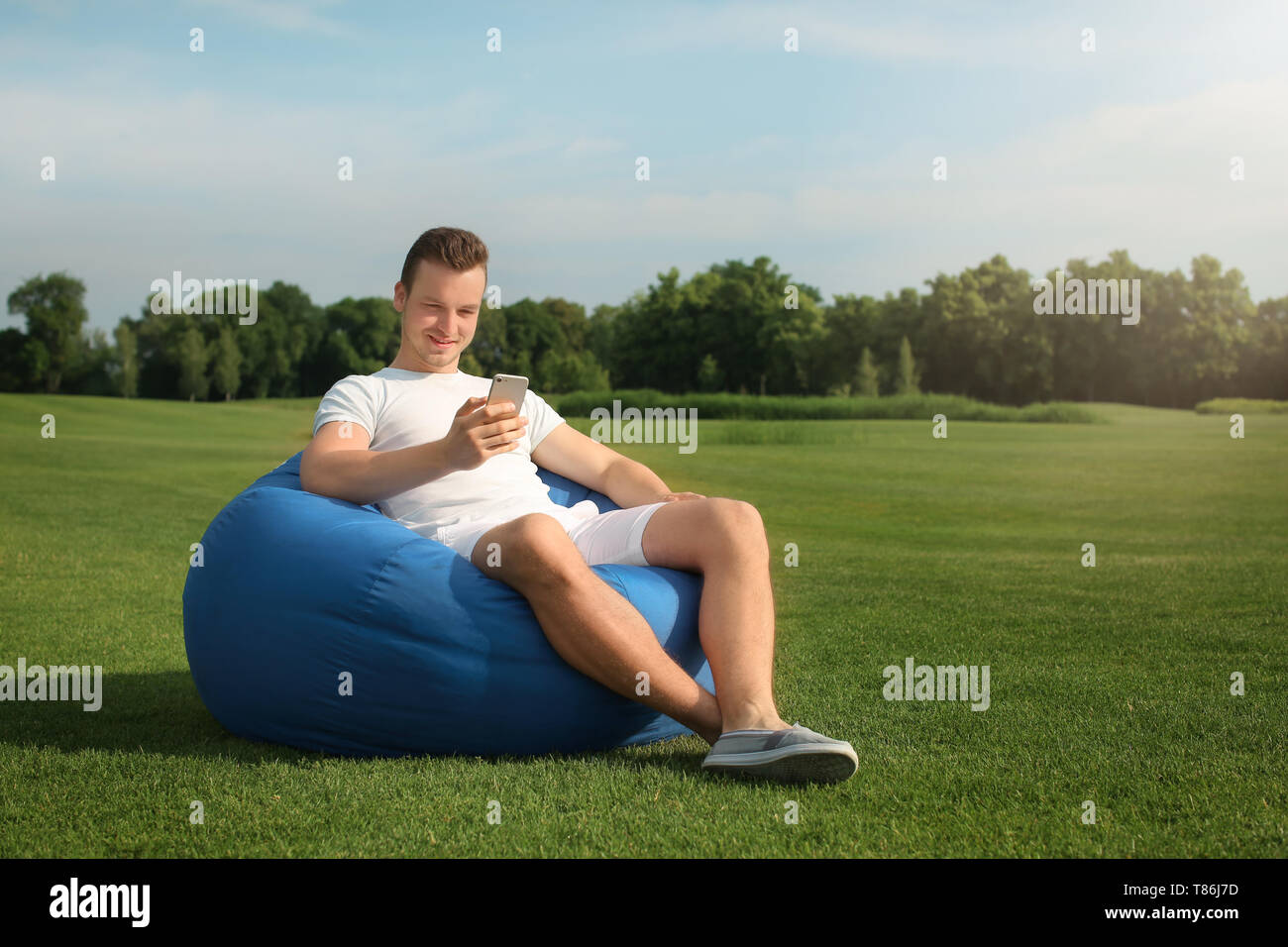 Young man with mobile phone resting on bean bag chair outdoors - Stock Image