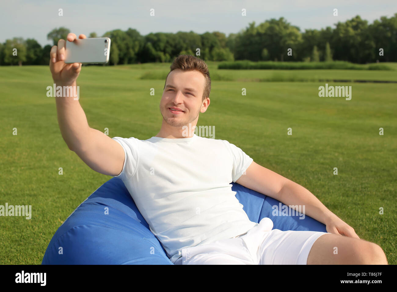 Young man taking selfie while sitting on bean bag chair outdoors - Stock Image