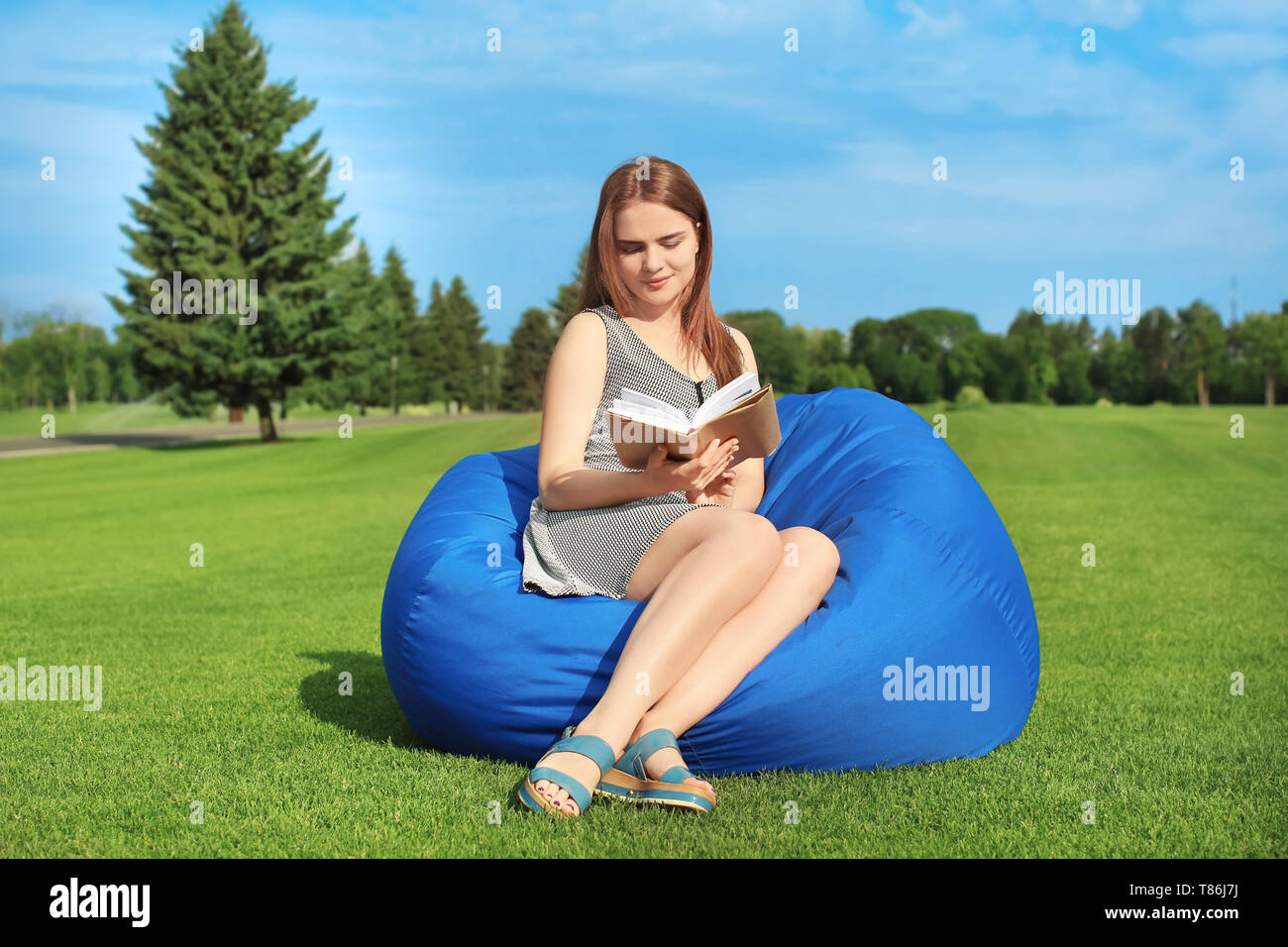 Young woman reading book while sitting on bean bag chair outdoors - Stock Image
