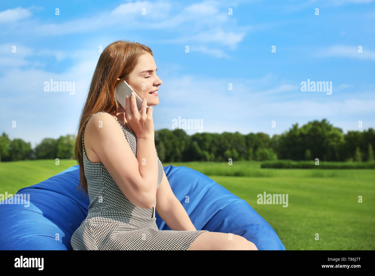 Young woman talking by mobile phone while sitting on bean bag chair outdoors - Stock Image