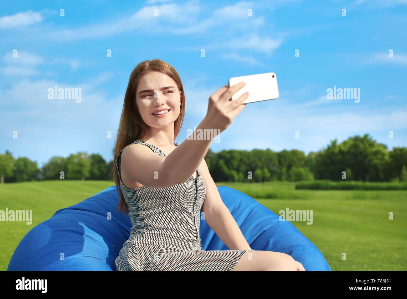 Young woman taking selfie while sitting on bean bag chair outdoors - Stock Image