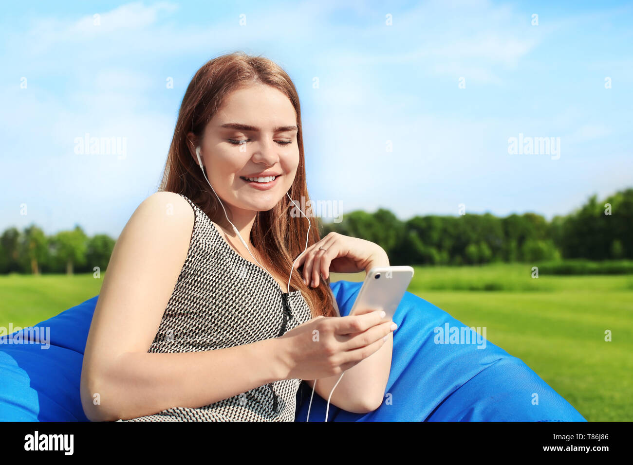 Young woman listening to music while sitting on bean bag chair outdoors - Stock Image