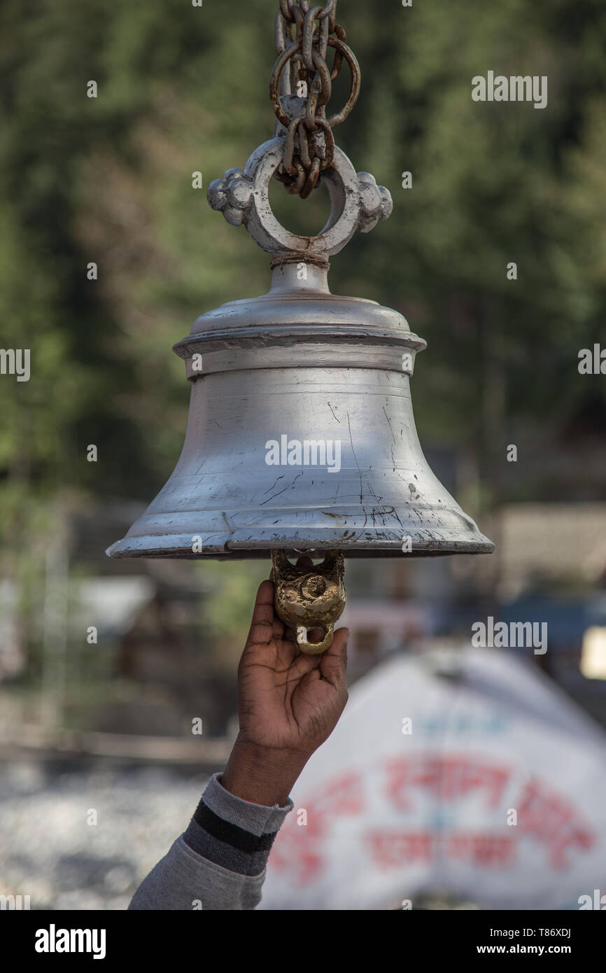 Silver temple bells hanging through chain and a devotee's hand trying to hit the bell at Gangotri in India - Stock Image
