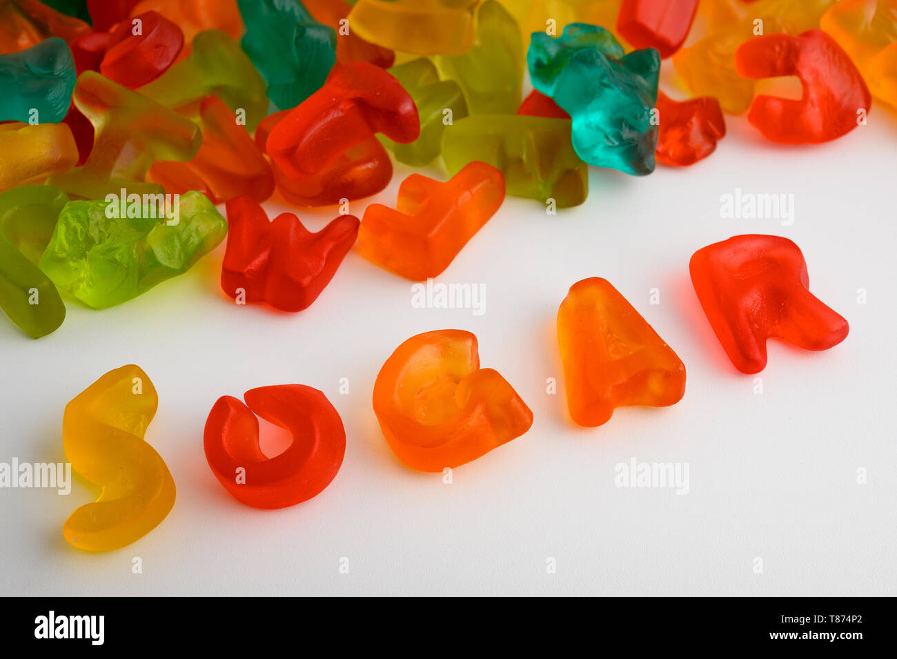 Colorful gummy candies on white background with the word SUGAR written with candies - Stock Image