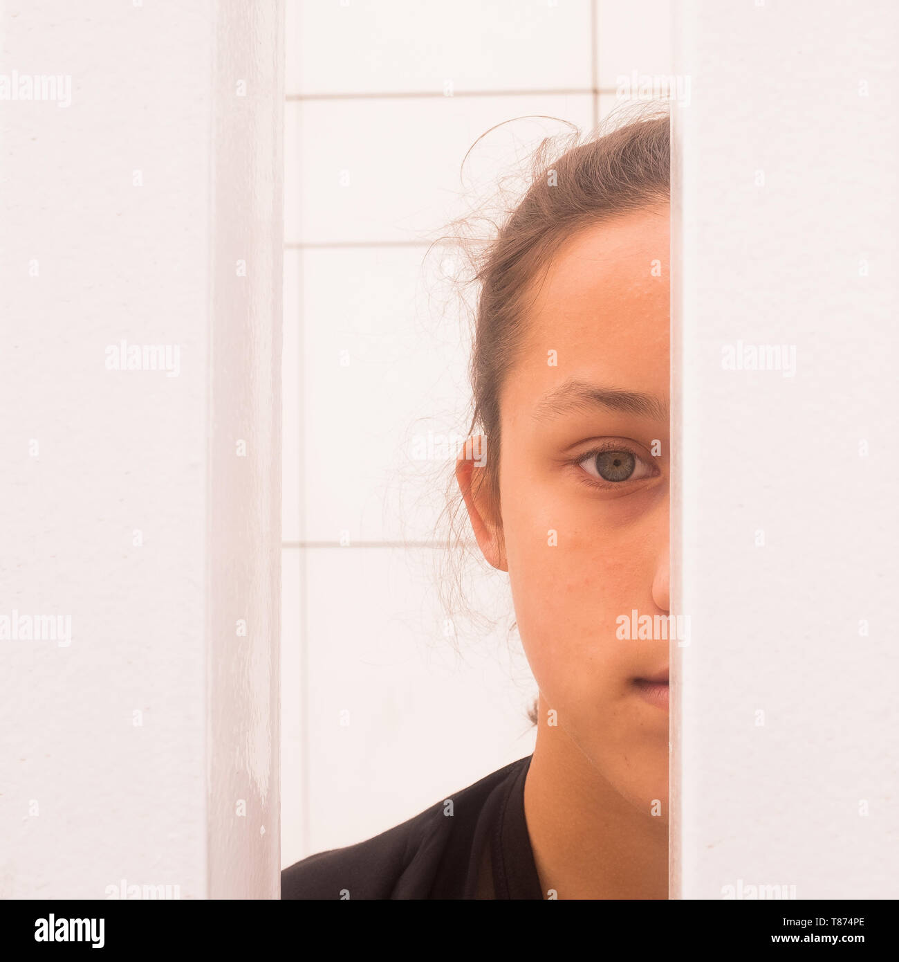 Close up half face portrait teenager girl looking through white metal bars, self-awareness and self worth concept, square image - Stock Image