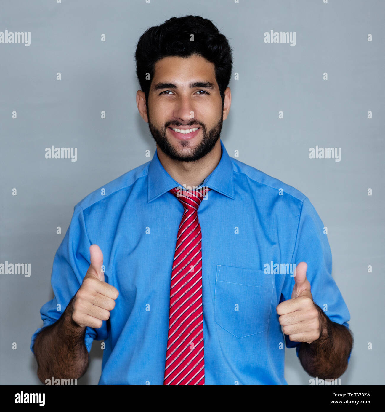 Portrait of successful latin american hipster businessman on grey background Stock Photo