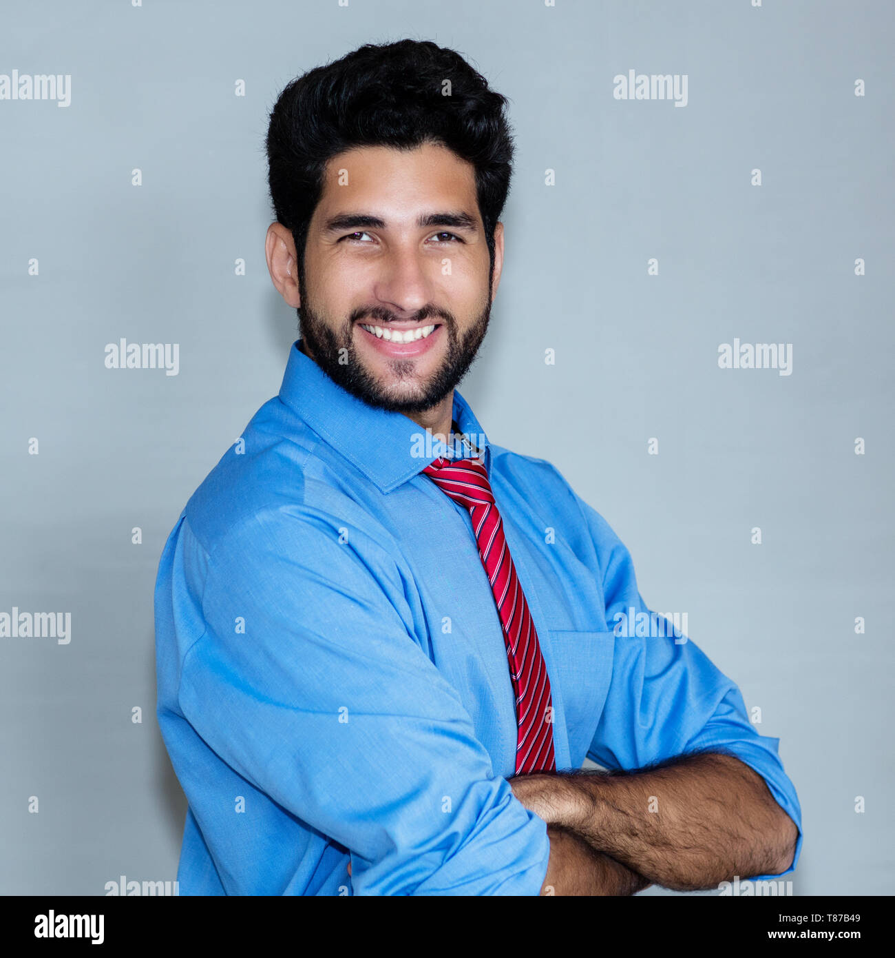 Portrait of laughing latin american hipster businessman on grey background - Stock Image