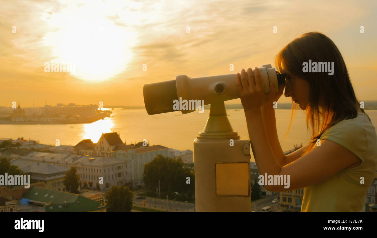 Young woman looking through tourist telescope, exploring historical part of city - Stock Image