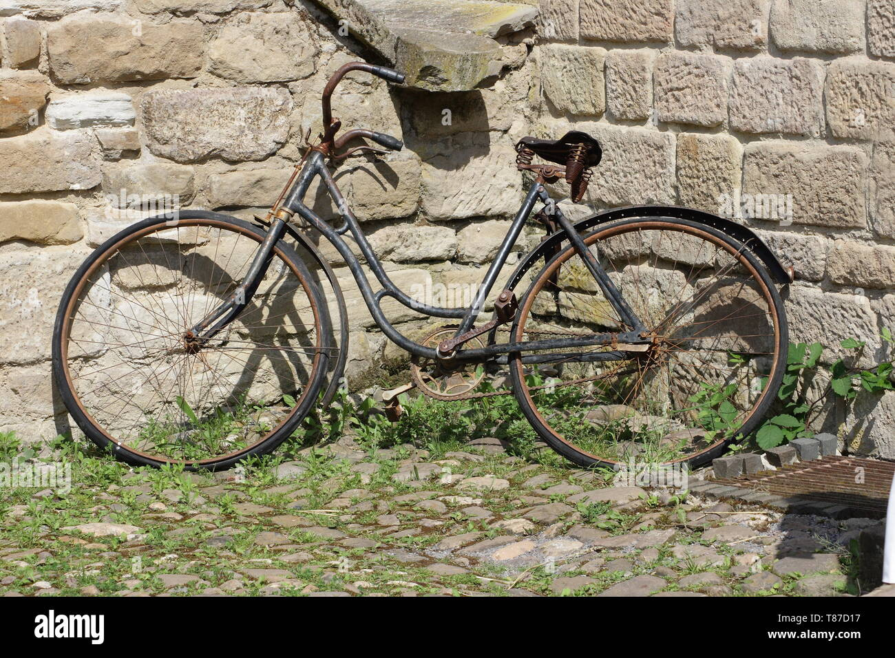old rusty bicycle parked against a wall Stock Photo
