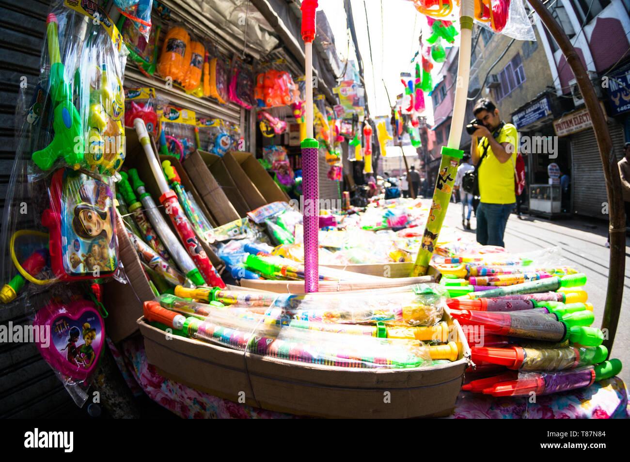 fisheye shot of a vendor selling holi supplies like water guns and colors - Stock Image