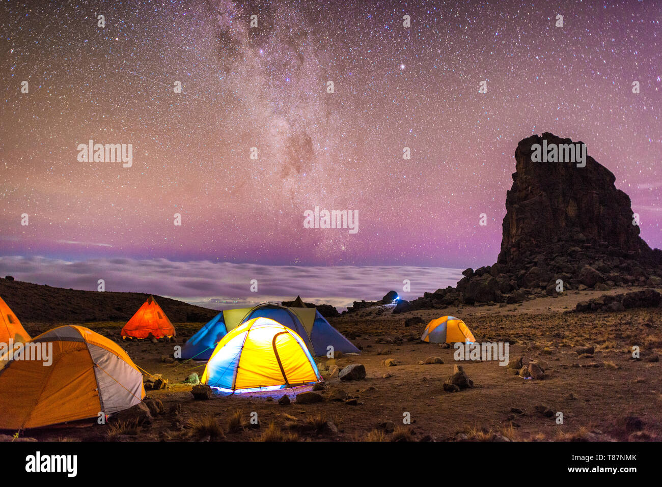 The brilliantly clear night sky at Lava Tower Camp (15,215 feet), with Lava Tower at right, clouds in the distance, and the Milky Way. Mt Kilimanjaro' - Stock Image