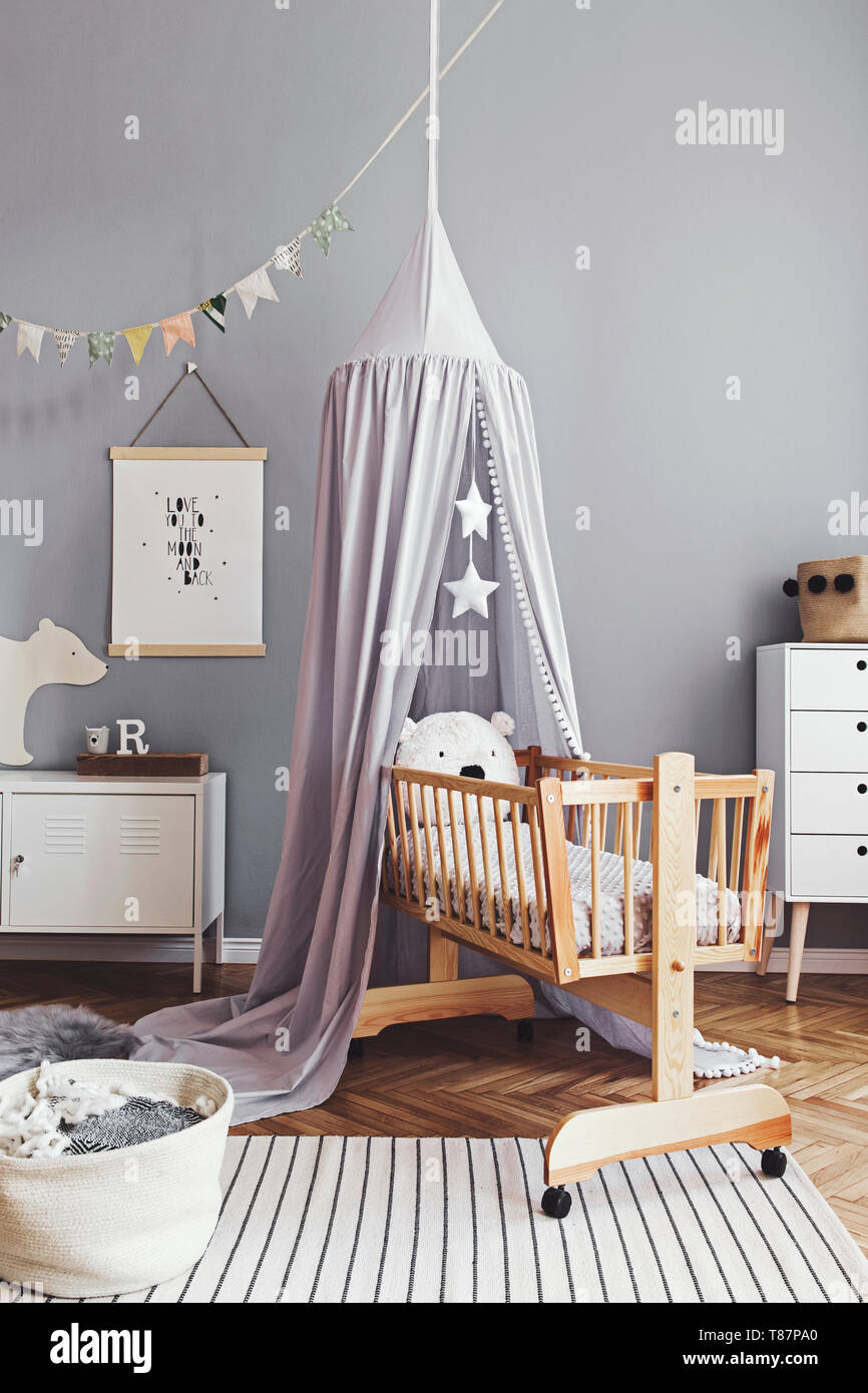 Stylish and modern scandinavian nursery interior with gray walls, brown wooden parquet and design furnitures and accessories. Cozy childroom. - Stock Image
