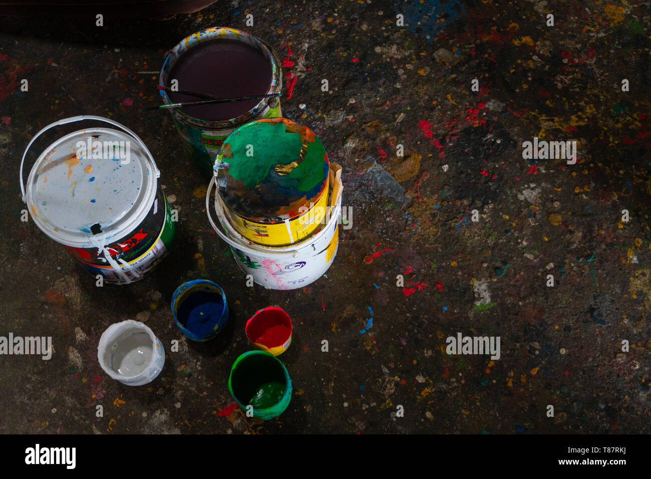 UBUD/BALI-APRIL 27 2019: colorful paint bucket with a brush and the floor is filled with beautiful solid color because the paint is scattered - Stock Image