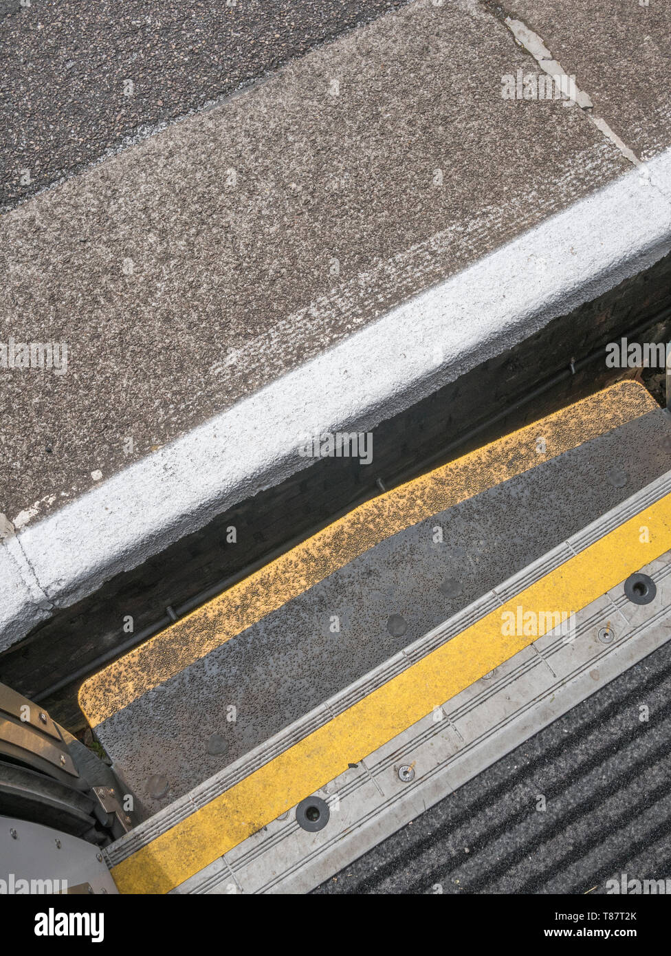 Gap between railway platform edge and railway carriage step painted yellow. Metaphor Mind the Gap, watch your step, gender gap, wage gap, warning. - Stock Image