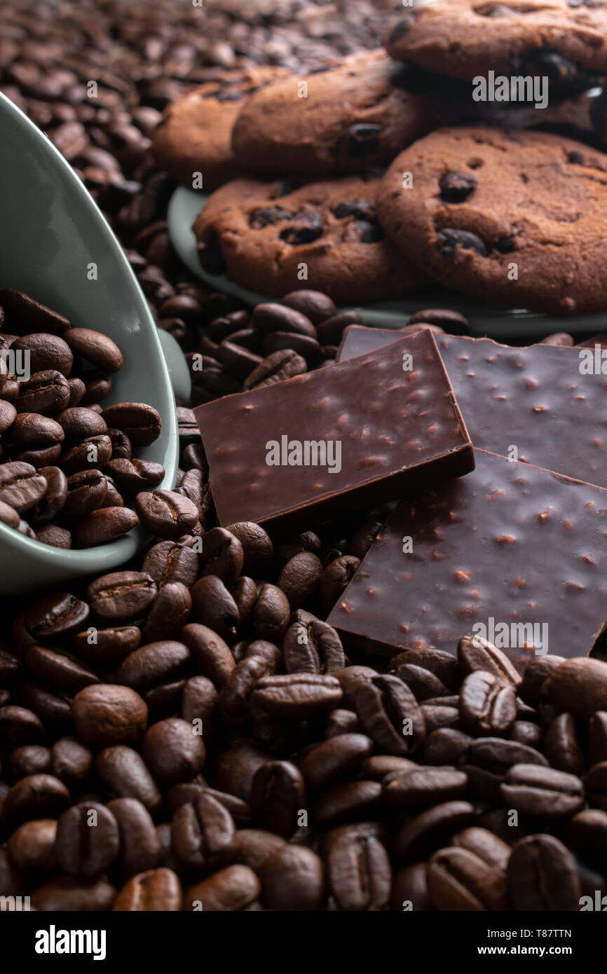 on coffee beansthe cup lies from it gets enough sleep coffee, opposite a chocolate bar, there are cookies behind Stock Photo