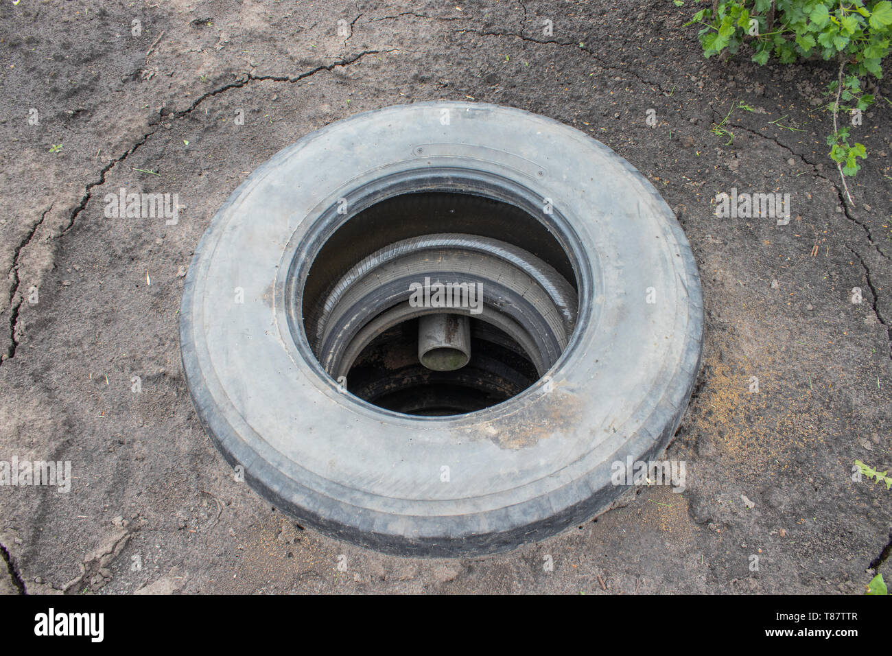 Sewer pit with car tires. Sewer system. - Stock Image