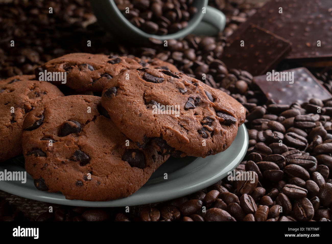 on coffee beansthe cup lies from it gets enough sleep coffee, opposite a chocolate bar, there are cookies behind - Stock Image